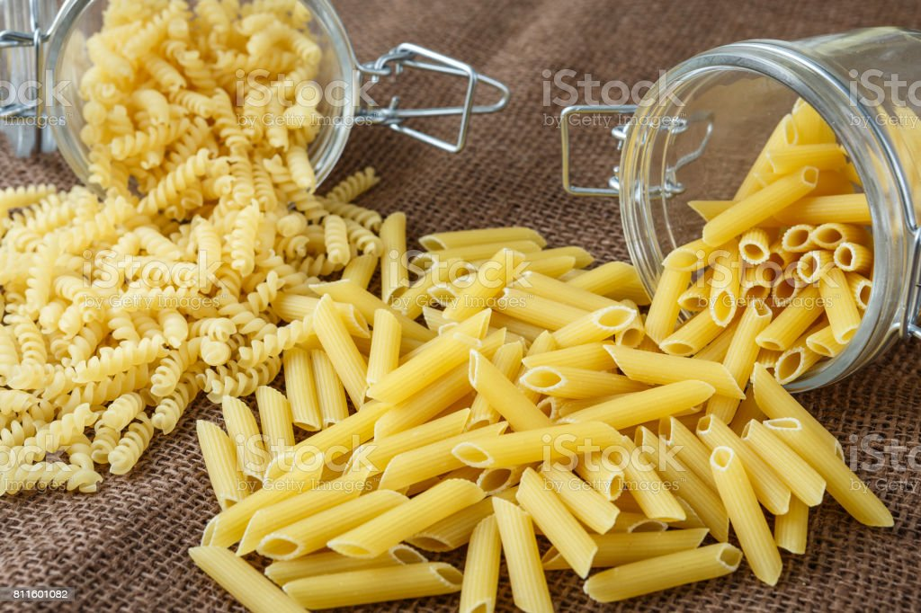 Italian pasta - penne and fusilli in glass jar on brown background stock photo