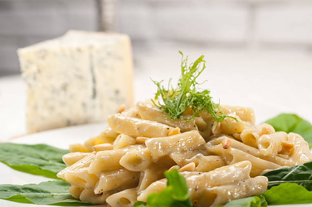 Italian pasta penne gorgonzola and pine nuts stock photo