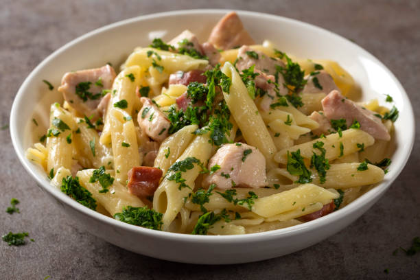 Italian pasta penne with chicken meat and bacon stock photo