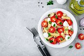 Italian pasta salad with tomatoes, mozzarella cheese, red onion and basil. Top view, copy space