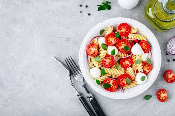 Italian pasta salad with tomatoes, mozzarella cheese, red onion and basil. Top view. Italian pasta salad with tomatoes, mozzarella cheese, red onion and basil. Top view, copy space fusilli stock pictures, royalty-free photos & images