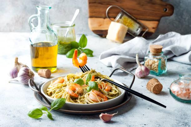 Italienische Pasta Spaghetti mit gegrillten Garnelen, Pestosauce und frischen Basilikumblättern – Foto