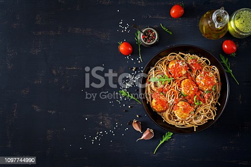 Italian pasta. Spaghetti with meatballs and parmesan cheese in black plate on dark rustic wood background.  Dinner. Top view. Slow food concept