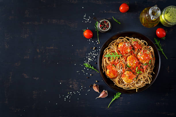 italian pasta. spaghetti with meatballs and parmesan cheese in black plate on dark rustic wood background.  dinner. top view. slow food concept - food stock pictures, royalty-free photos & images