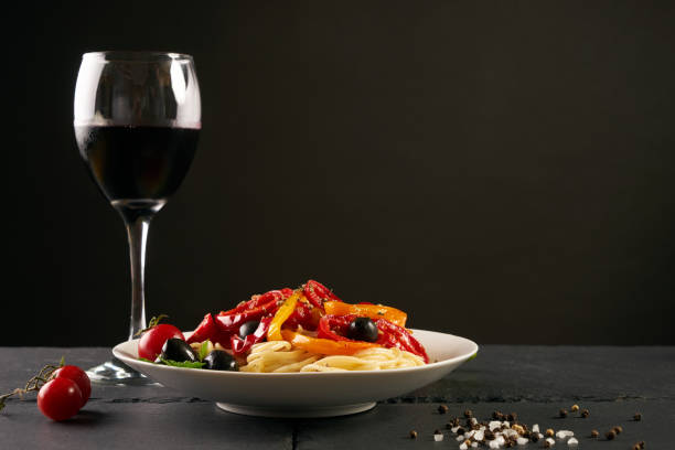 italienische pasta mit einem parmesan käse basilikum oliven paprika und tomaten auf einem weißen teller auf einer dunklen schiefer auf schwarzem hintergrund mit textfreiraum isoliert. - weinsoße stock-fotos und bilder