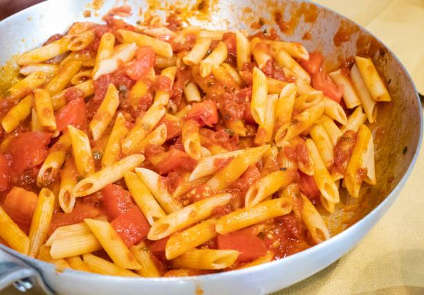Italian pasta with garlic and oil and diced tomato, pennette rigate pasta, Italian recipe in the pot stock photo