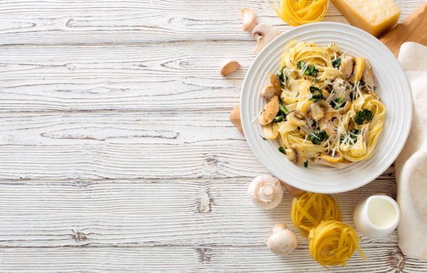 Italian pasta( fettuccini) with mushrooms, chicken meat, spinach and cream sauce stock photo