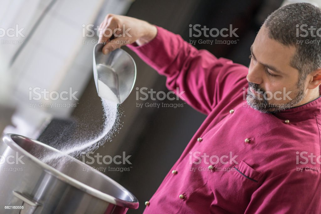 Italian pastry making patisserie baking confectioner: Adding sugar stock photo