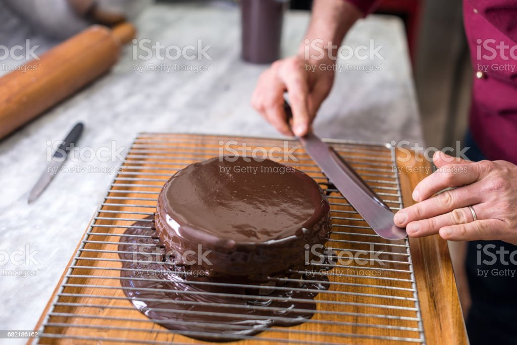 Italian pastry making patisserie baking confectioner: Covering sachertorte with chocolate stock photo