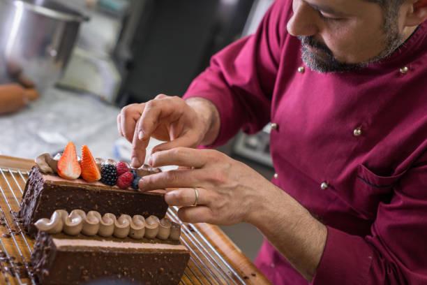 italienischen gebäck machen konditorei konditor backen: kuchen mit früchten dekorieren - italienische küchen dekor stock-fotos und bilder