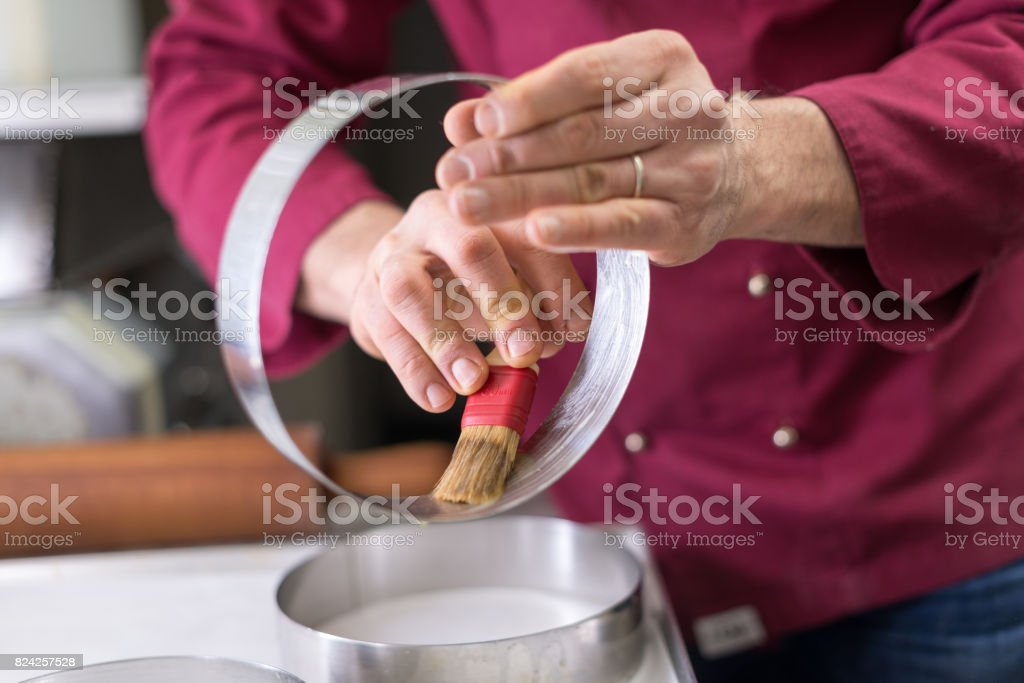 Italian pastry making patisserie baking confectioner: lubricating cake rings with butter stock photo