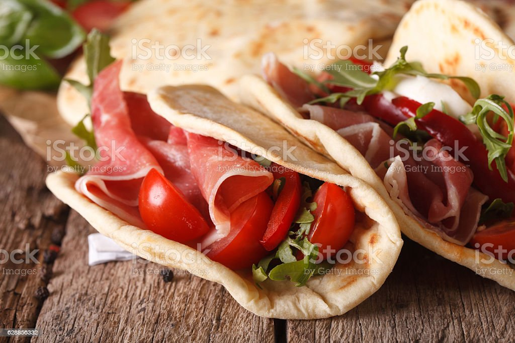 Italian piadina flatbread stuffed with ham and vegetables close-up stock photo