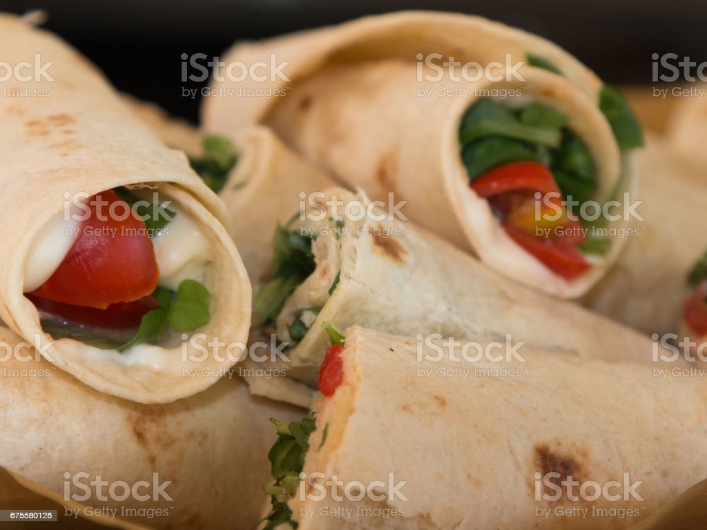Italian Piadina Rolled and Filled with Cheese, Tomato and Argula: Typical Italian Sandwich Flat unleavened Bread stock photo