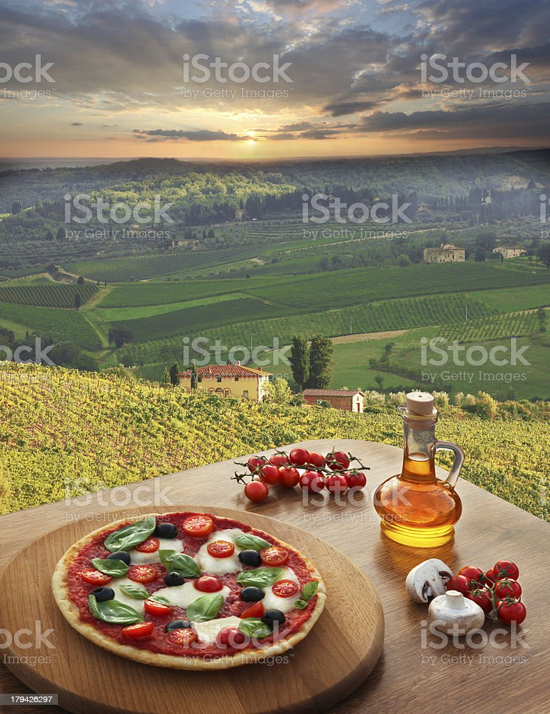 Italian pizza against vineyard landscape in Italy royalty-free stock photo