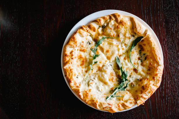 italiaanse pizza vier kaas met rucola op een bruine houten bureau achtergrond. quattro formaggi. van boven. heerlijke warme pizza op een wit bord. golz. - dikke pizza close up stockfoto's en -beelden