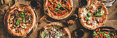 Pizza party dinner. Flat-lay of various kinds of Italian pizza, salad and red wine in glasses over rustic wooden table, top view, wide composition. Fast food lunch, celebration, gathering concept