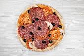 istock Italian pizza on white wooden background 1252940269