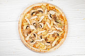 istock Italian pizza on white wooden background 1252940279