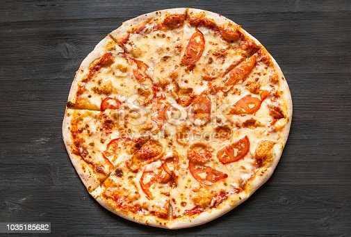 top view of italian pizza with mozzarella cheese and tomatoes on dark brown wooden board