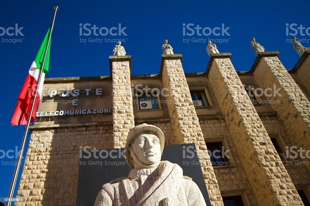 The Italian flag flies outside the central post office in Ragusa,...