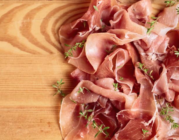 italienischen prosciutto crudo oder jamon mit thymian auf einem holztisch. - thymian trocknen stock-fotos und bilder