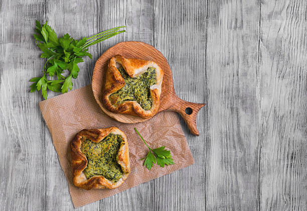 Italian puff pastry patties fagottini Italian puff pastry patties fagottini stuffed with cheese and spinach, parsley on a light background white wooden, top view hot pockets stock pictures, royalty-free photos & images