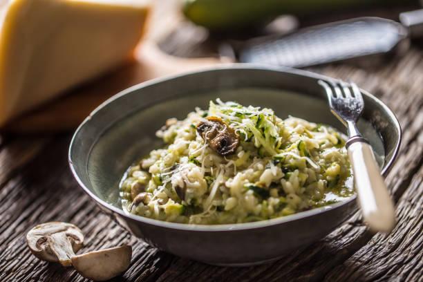 Italienische Risotto-Zucchini-Pilze und Parmesan in dunkler Platte – Foto
