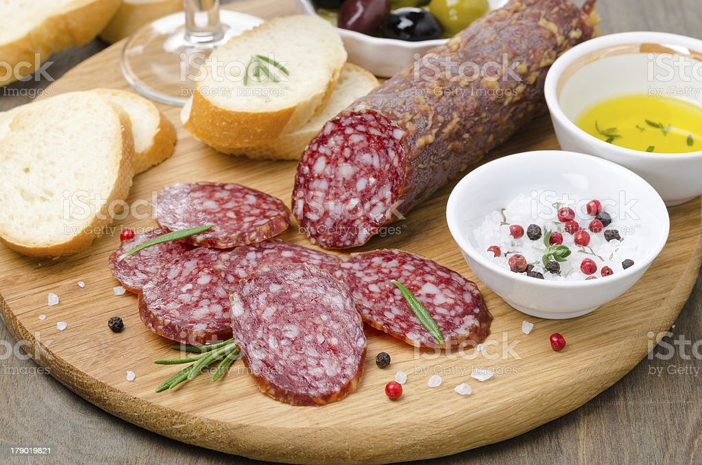 Italian salami, bread and spices on a cutting board royalty-free stock photo