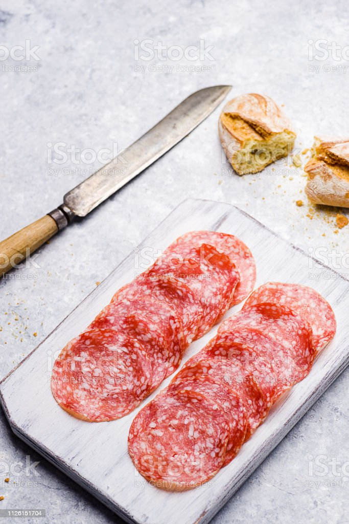 italian salami on small cutting board on delicate background - foto stock