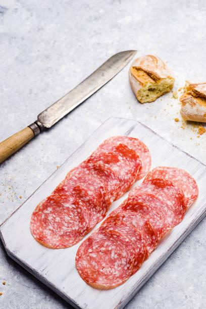italian salami on small cutting board on delicate background - foto stock