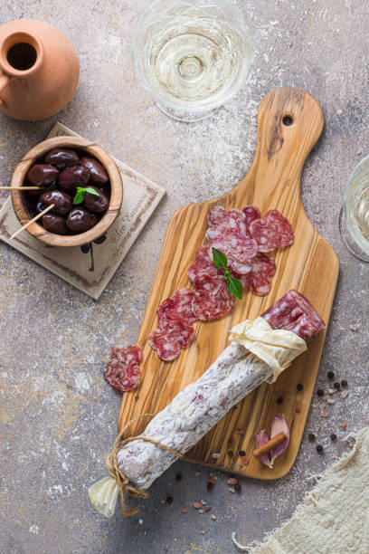 Italian salami on wooden board with cheese and olives stock photo