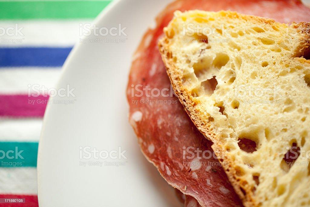 Italian Salami Sandwich on Color Striped Tablecloth stock photo