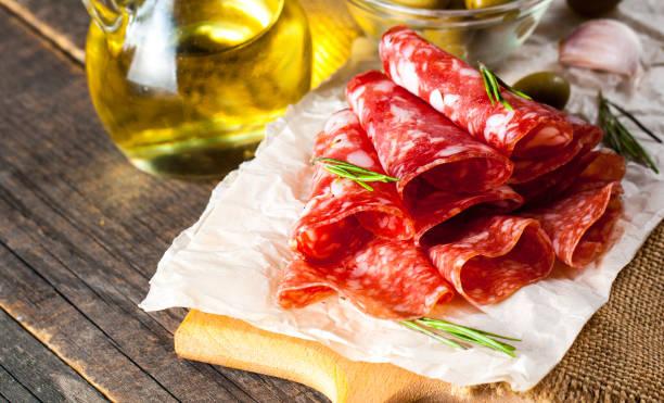 italienische salami mit oliven und gewürzen auf hölzernen hintergrund - pökeln stock-fotos und bilder