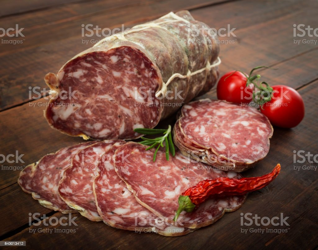 Italian salami with red pepper cherry tomatoes on a wooden background stock photo