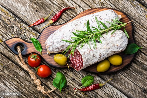 Italian salami with rosemary, pepper, cherry tomatoes and olives on a wooden background. Top view
