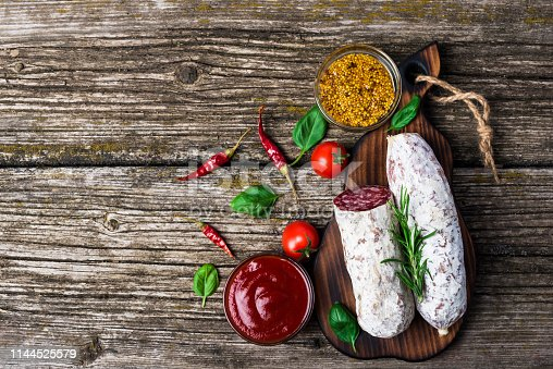 Italian salami with rosemary, pepper, cherry tomatoes and olives on a wooden background. Banner. Top view