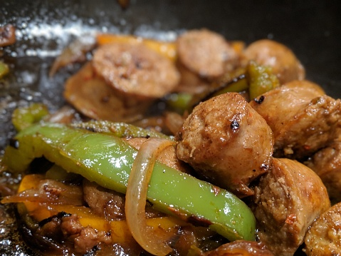 Yellow and green bell peppers cooking with onions and Italian sausage