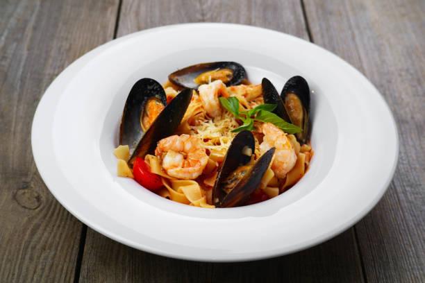 italienischer meeresfrüchte pasta mit muscheln und garnelen - pasta deli stock-fotos und bilder