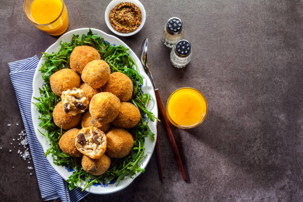 Italian snack. Fried balls from rice Arancini with mushrooms, cheese with mustard sauce and a salad of rucola on a gray stone table with freshly squeezed orange juice. fast healthy hearty meal stock photo