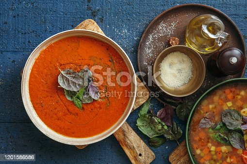 Vegan tomato and minestrone soups on dark blue background. Top view.