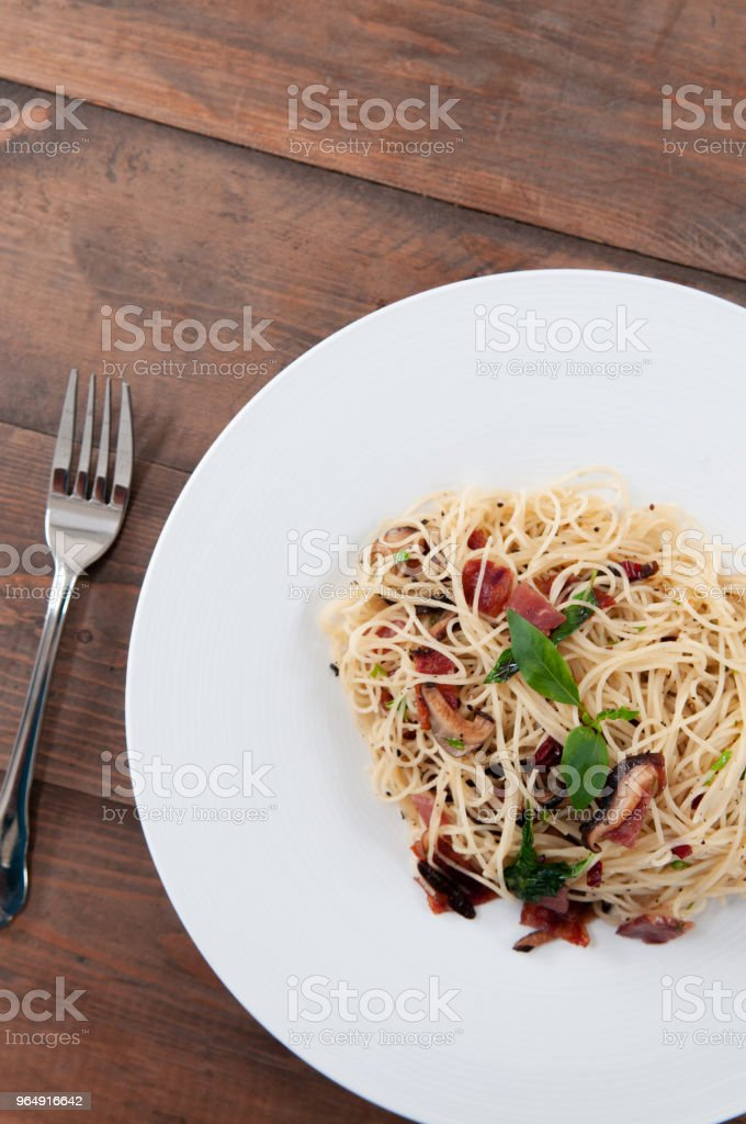 Italian Spaghetti pasta bacon with dried spicy chilli on white plate on the wood table from top view royalty-free stock photo