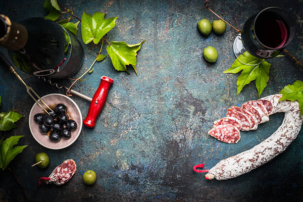 Italian still life with salami, wine, olives and grape leaves stock photo