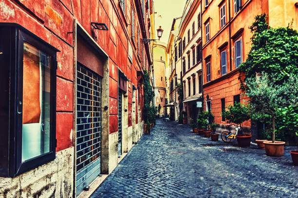 italian street with facade garages, flowerpots and bright buildings - rome road central view foto e immagini stock