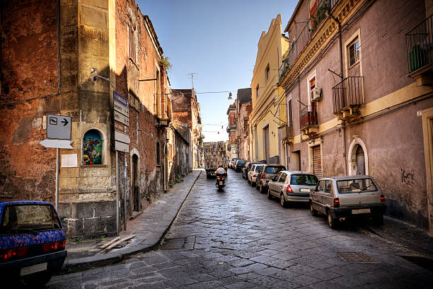 Italian Streetlife Moped and delivery truck speed down a narrow alley in the Sicilian town of Catania. catania stock pictures, royalty-free photos & images