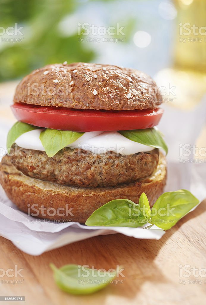 Italian style burger with mozzarella cheese, basil and tomatoes stock photo