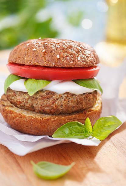 Italian style burger with mozzarella cheese, basil and tomatoes stock photo