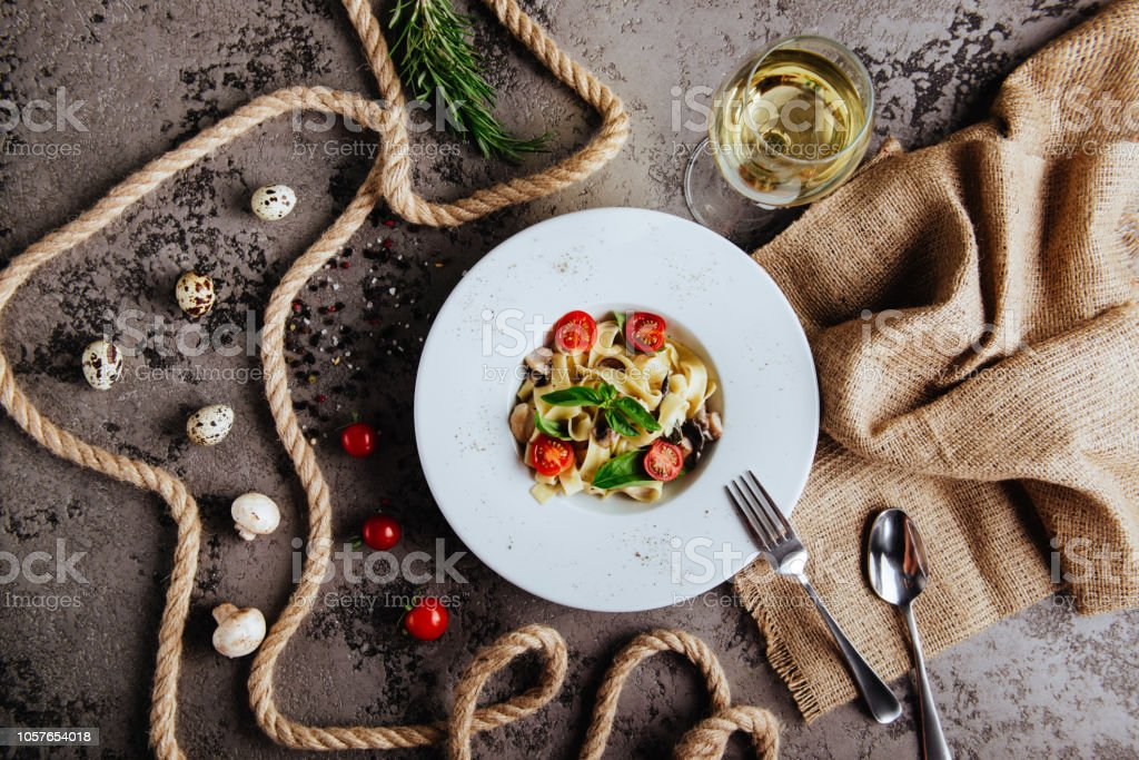 Italian style pasta dinner. Spaghetti with tomato and basil in plate on wooden board stock photo