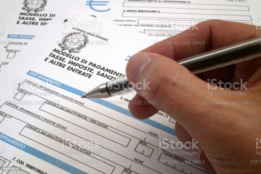 Italian tax form Hand of somebody filling an Italian tax form (Mod. F23). Concepts Stock Photo