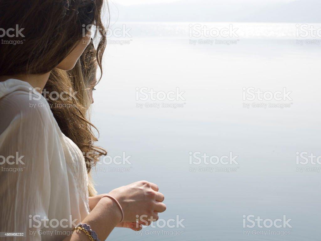 Italian Teenage Girls Look Across Lake From Edge Royalty Free Stock Photo