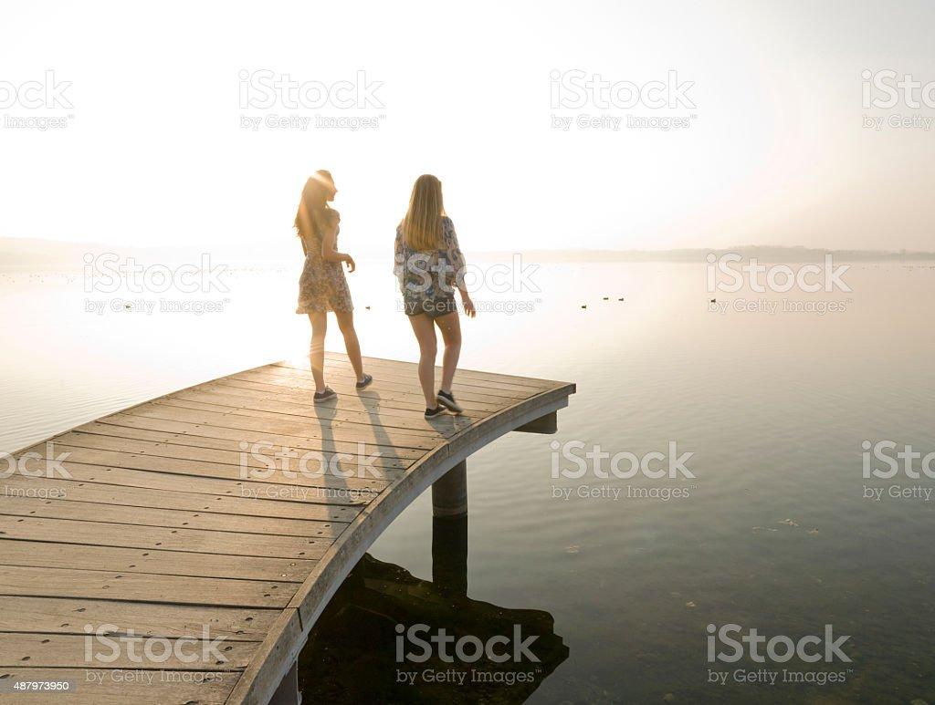 Italian Teenage Girls Walk Along Wooden Pier By Lake Royalty Free Stock Photo